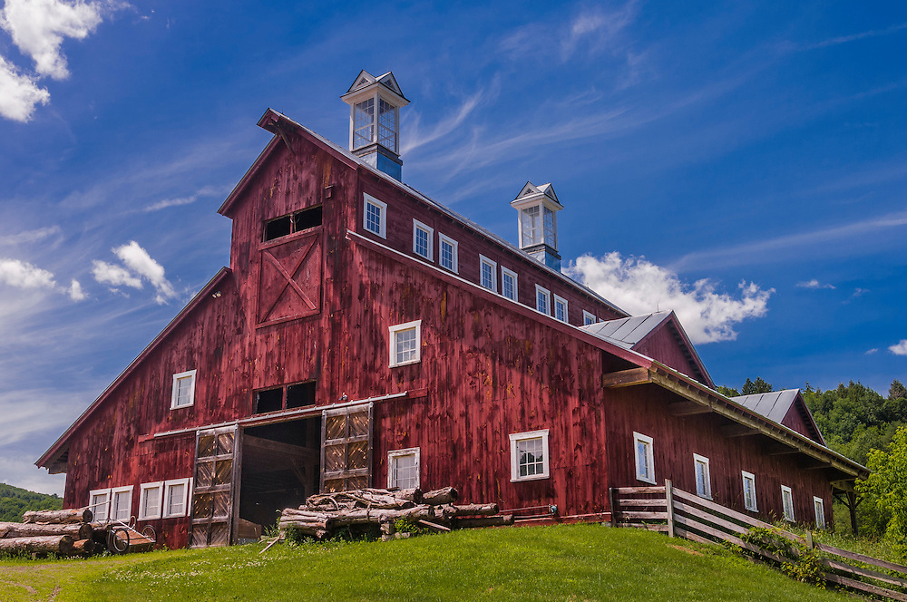 Big red barn with interesting architecture in summer under a blue sky, Royalton, VT