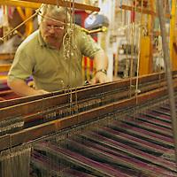 Europe, Ireland, Avoca. Avoca Handweavers Mill, County Wicklow. Weaver at woollen handweaving loom.