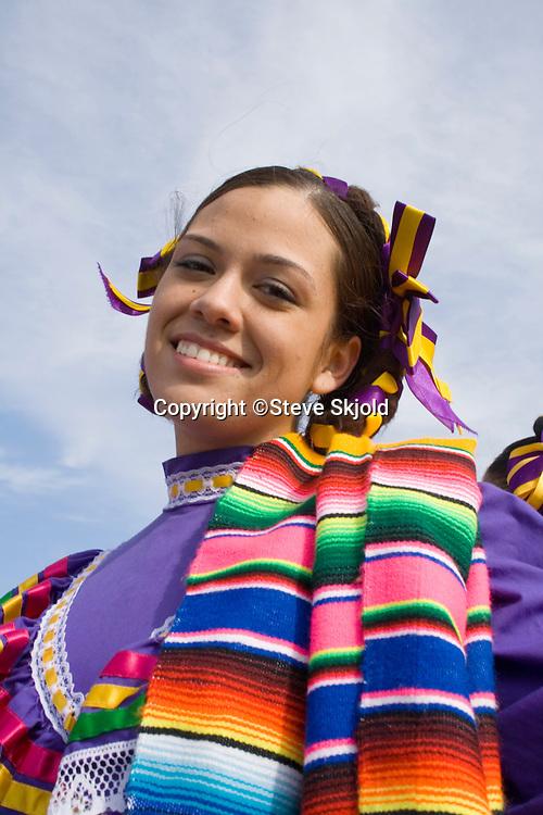 Hispanic teen displaying her beautiful traditional Mexican dress. Cinco de Mayo Fiesta St Paul Minnesota USA