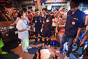 """02 OCTOBER 2009 -- BANGKOK, THAILAND: Members of the public and volunteers from the Poh Teck Tung Foundation gather around the body of a man who died in a motorcycle accident in Bangkok. The 1,000 plus volunteers of the Poh Teck Tung Foundation are really Bangkok's first responders. Famous because they pick up the dead bodies after murders, traffic accidents, suicides and other unplanned, often violent deaths, they really do much more. Their medics respond to medical emergencies, from minor bumps and scrapes to major trauma. Their technicians respond to building collapses and traffic accidents with heavy equipment and the """"Jaws of Life"""" and their divers respond to accidents in the rivers and khlongs of Bangkok. The organization was founded by Chinese immigrants in Bangkok in 1909. Their efforts include a hospital, college tuition for the poor and tsunami relief.   PHOTO BY JACK KURTZ"""