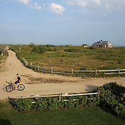 A teenage boy on a bike heads back along a track from Cisco Beach, Nantucket, Nantucket Island, Massachusetts, USA. Photo Tim Clayton