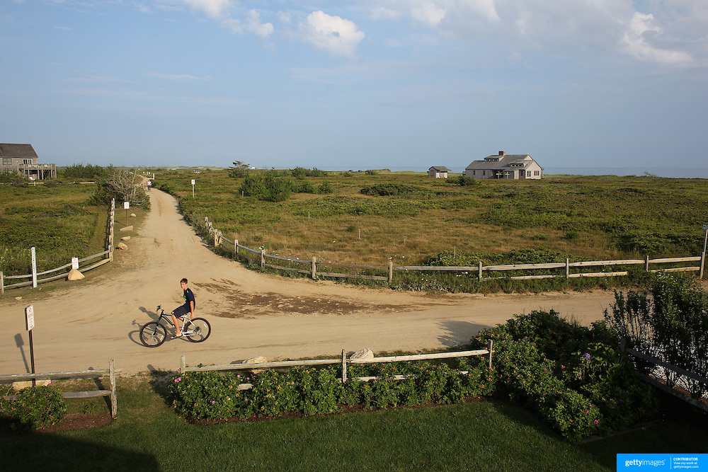 A teenage boy on a bike heads back along a track from Cisco Beach, Nantucket, Nantucket Island, Massachusetts, USA. Photo Tim Clayton