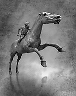 'Jockey of Artrmision' a Hellenistic bronze statue of a boy riding a horse. National Archaeological Museum Athens. Circa 140 BC. Cat No X 15177. Black and White Wall art print by Photographer Paul E Williams . Retrieved in pieces from a shipwreck of Cape Artemision in Euboea. The young jockey holds a rein in his left hand and a whip in his right. His face has a passionate expression with furrowas on his face. The pieces of the Bronze sculpture were reassembled in 1971.