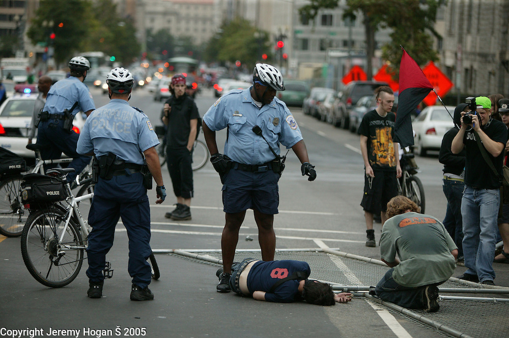 A Black Bloc Anarchist lies on the ground before being arrested by police during the anti-war march on Washington. A group of about 150 anarchist marched through the streets for a couple hours before police made severals arrests.