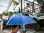 11 SEPTEMBER 2015 - BANGKOK, THAILAND:  A woman walks by a house being torn down at Wat Kalayanamit. Authorities started to destroy 54 homes in front of Wat Kalayanamit, a historic Buddhist temple on the Chao Phraya River in the Thonburi section of Bangkok. Government officials, protected by police, seized the house of Chaiyasit Kittiwanitchapant, a Kanlayanamit community leader, who has led protests against the temple's abbot for trying to evict community members whose houses are located around the temple. Work crews went into Chaiyasit's home and took it apart piece by piece. The abbot of the temple said he was evicting the residents, who have lived on the temple grounds for generations, because their homes are unsafe and because he wants to improve the temple grounds. The evictions are a part of a Bangkok trend, especially along the Chao Phraya River and BTS light rail lines, of low income people being evicted from their long time homes to make way for urban renewal.        PHOTO BY JACK KURTZ