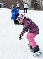 Nine year old Natalie Fraser tries a snowboarding lesson from Gary Chase to start off the season at Gunstock Mountain Resort Saturday afternoon.  (Karen Bobotas/for the Laconia Daily Sun)