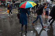 A lady with a Legal & General brolly, carefully steps through rain water as Storm Georgina sweeps across parts of Britain and in central London, lunchtime office workers were caught out by torrential rain and high winds, on 24th January 2018, in London, England. Pedestrians resorted to leaping across deep puddles at the junction of New Oxford Street and Kingsway at Holborn, the result of overflowing drains.