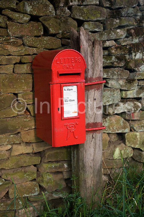 A rural red Victorian post box mounted on a dry stone wall in the Vale of Edale, Peak District National Park, Derbyshire. The distinctive letter VR denote the box's age, meaning Victoria Regina as opposed to GR for King George or currently ER, for Queen Elizabeth. We also see daily postal collection times on the label. Edale is a valley in North Derbyshire, situated about 15 miles west of Sheffield, a loose collection of scattered farmsteads or 'booths' as they are known which grew up around the original shelters or 'boothies' used by shepherds when tending their sheep on the hillsides. There are 5 main ones in Edale valley, Nether Booth, Ollerbooth, Upper Booth, Barber booth and Grindsbrook Booth of which the village called Edale is part.
