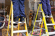 Mannequins in a shop window juxtapose with the lower legs of workmen up two set of ladders in London.