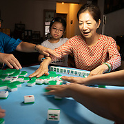 Elaine HAU Wai-lin, owner of a street restaurant in Hong Kong, plays mahjong at home.