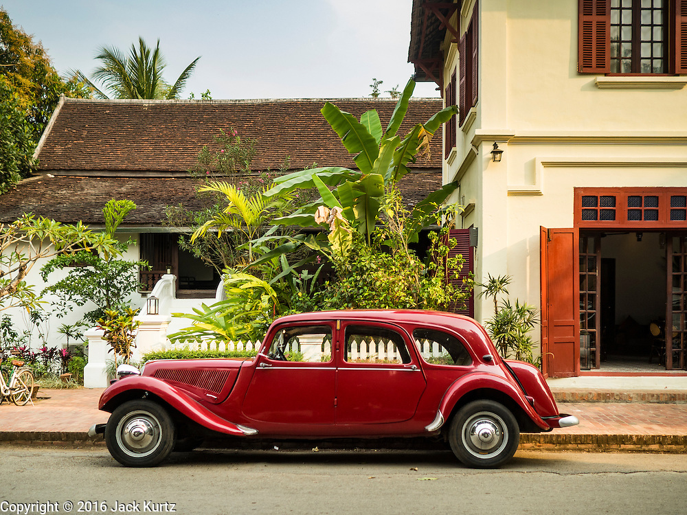 """12 MARCH 2016 - LUANG PRABANG, LAOS:  A1952 Citroen Model 11, one of only two of that model in Laos, at 3 Nagas, one of the most upscale hotels in Luang Prabang. Luang Prabang was named a UNESCO World Heritage Site in 1995. The move saved the city's colonial architecture but the explosion of mass tourism has taken a toll on the city's soul. According to one recent study, a small plot of land that sold for $8,000 three years ago now goes for $120,000. Many longtime residents are selling their homes and moving to small developments around the city. The old homes are then converted to guesthouses, restaurants and spas. The city is famous for the morning """"tak bat,"""" or monks' morning alms rounds. Every morning hundreds of Buddhist monks come out before dawn and walk in a silent procession through the city accepting alms from residents. Now, most of the people presenting alms to the monks are tourists, since so many Lao people have moved outside of the city center. About 50,000 people are thought to live in the Luang Prabang area, the city received more than 530,000 tourists in 2014.      PHOTO BY JACK KURTZ"""