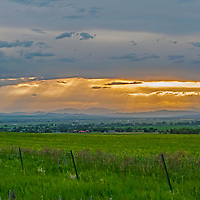 The sun's rays poke between clouds over the Gallatin Valley near Bozeman and Belgrade, Montana.