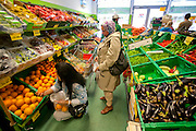 The Qureshi family of Lorenskog, Norway, an Oslo suburb. Pritpal Qureshi, 49, kneeling, choosing fruit in an ethnic market in Oslo while buying a week's worth of groceries.