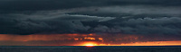 Sun Rising Under the Clouds. Panorama from the aft deck of the MV World Odyssey. Composite of 2 mages taken with a Nikon 1 V3 camera and 70-300 mm lens (ISO 200, 70 mm, f/11, 1/60 sec).  Raw images processed with Capture One Pro and AutoPano Giga Pro.