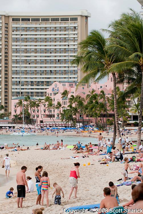 Waikiki beach full of people with the pink Royal Hawaiian Hotel and Sheraton Waikiki in the background.