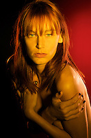 Portrait of a very sensual redhair woman with suggestive looking, in red light.