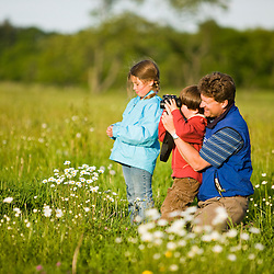 A man and his two children bird watching in a hay field on a farm in Ipswich, Massachusetts.