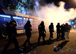 September 20, 2016 - Charlotte, North Carolina, U.S. - Charlotte-Mecklenburg police officers walk through a haze of tear gas on Old Concord Rd. on Tuesday night. The protest began on Old Concord Road at Bonnie Lane, where a Charlotte-Mecklenburg police officer fatally shot a man in the parking lot of The Village at College Downs apartment complex Tuesday afternoon. The man who died was identified late Tuesday as Keith Scott, 43, and the officer who fired the fatal shot was CMPD Officer Brentley Vinson. (Credit Image: © Jeff Siner/TNS via ZUMA Wire)