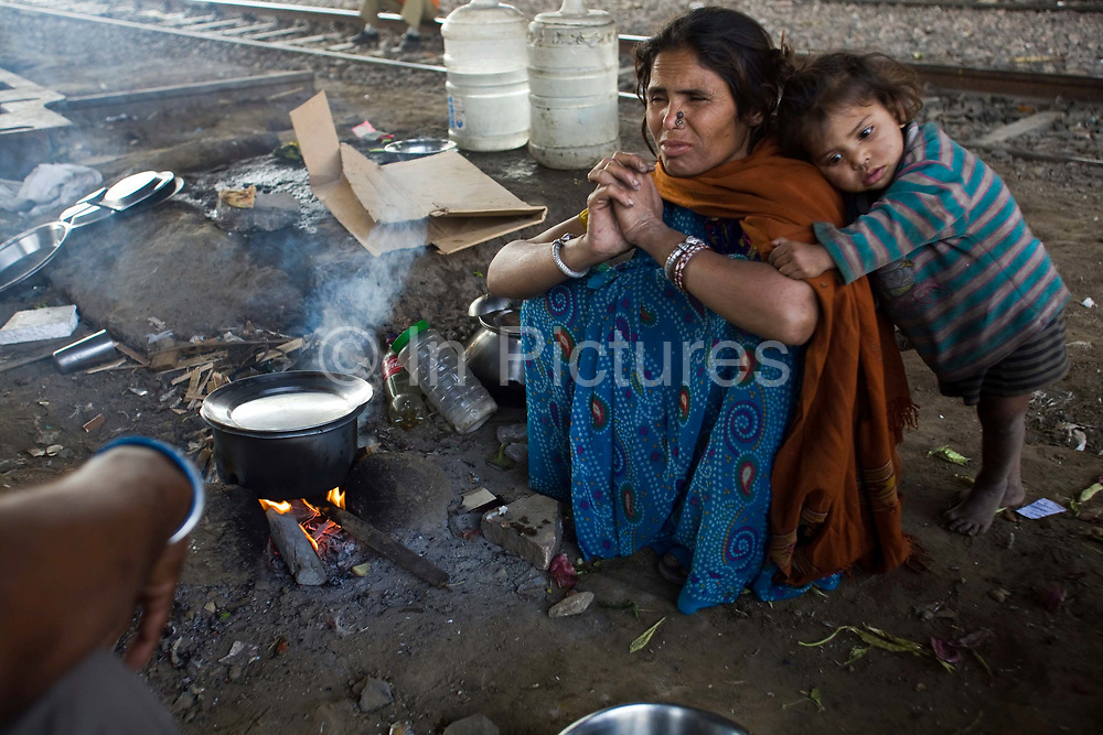 Aarti cooks breakfast on a piece of waste ground beneath a flyover near Okhla station. New Delhi, India.