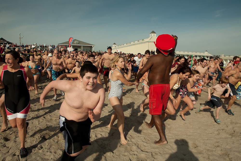 Charles Johnson, a resident of Wakefield, in the red trunks and red hat, encouraging the corwd to jump in the water for the annual Pier Swim, held at the Narragansett Town Beach on New Year's Day.