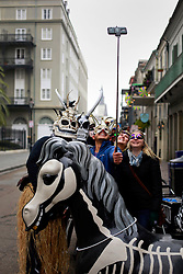 17 Feb 2015. New Orleans, Louisiana.<br /> Mardi Gras Day. Walking with Skeletons. <br /> A turist with a selfie stick stops to take a photo with the Krewe as they entering the French Quarter. The Skeleton Krewe meets before dawn beside a cemetery in Uptown New Orleans. They then walk several miles Along Saint Charles Avenue to the French Quarter to celebrate Mardi Gras Day.<br /> Photo; Charlie Varley/varleypix.com