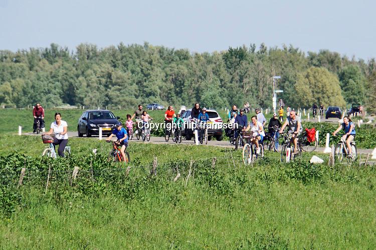Nederland, Nijmegen, 25-4-2020  Tijdens dit warme weekend was het voor veel mensen moeilijk thuis te blijven . Beeld van de drukte op de waaldijk in de Ooijpolder.Foto: Flip Franssen