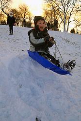 Child sledging in snow in winter; Cumbria UK