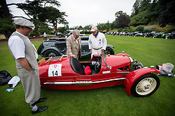 © Licensed to London News Pictures. 13/07/2015. Epsom, UK. Classic car enthusiast examine a 1933 Morgan 3 wheeler while on display before the race. The start of The Royal Automobile Club 1000 Mile Trial 2015 at Woodcote Park in Epsom, Surrey. The event, which starts and finishes at Woodcote Park, takes a fleet of over 40 classic cars from around the world, through a 1000 mile trial around the UK.  Photo credit: Ben Cawthra/LNP