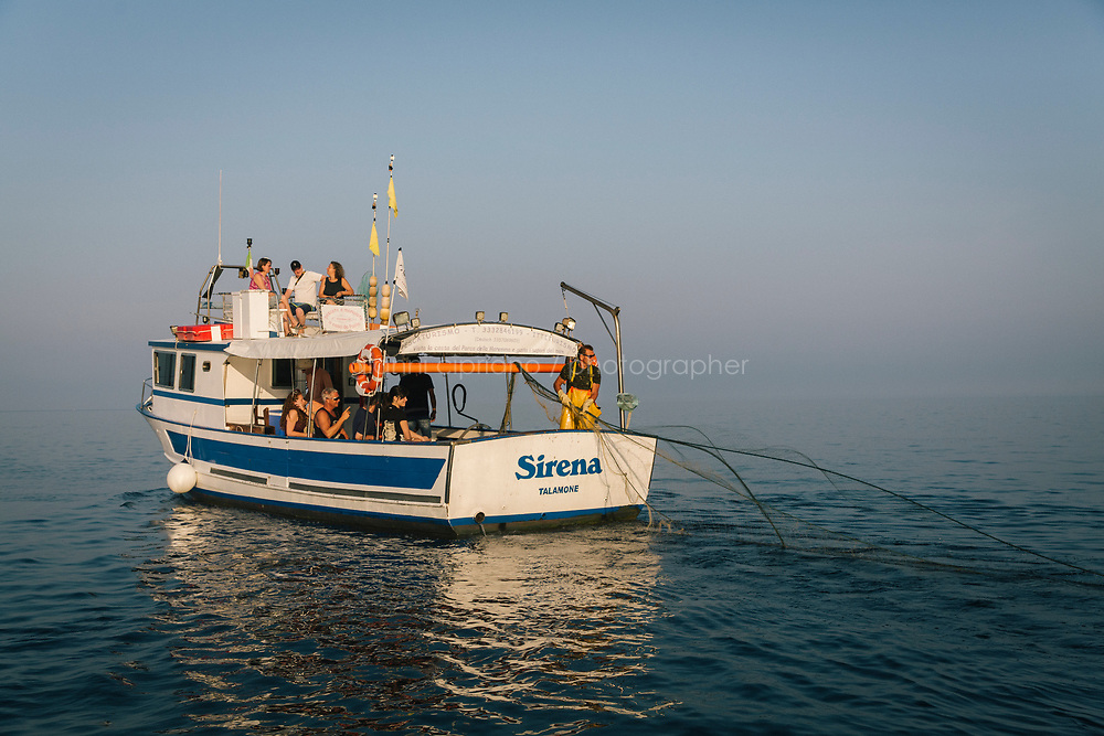 """TALAMONE, ITALY - 27 AUGUST 2019: Fisherman and activist Paolo Fanciulli (58) throws fishing nets from his """"Sirena"""" boat as visitors watch him work,  in Talamone, Italy, on August 27th 2019.<br /> <br /> In 2006, fisherman Paolo Fanciulli used government funds and the donations from his loyal excursion clients to fund a project in which they protected the local waters from trawling by dropping hundreds of concrete blocks around the seabed. But his true dream was to lay down works of art down on the sea floor off the coast of Tuscany. His underwater art dreams came true when the owner of a Carrara quarry, inspired by Mr. Fanciulli's vision, donated a hundred marble blocks to the project.<br /> Mr. Fanciulli invited sculptors to work the marble and set up kickstarter accounts, boat tours and dinners to fund the project. The acclaimed British artist Emily Young carved a ten-ton """"Weeping Guardian"""" face, which was lowered with other sculptures into the water in 2015.<br /> Since then, coral and plant life have covered the sculptures and helped bring back the fish. And Paolo the Fisherman is catching as many of them as he can."""