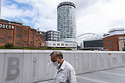 As numbers of Covid-19 cases in Birmingham have increased dramatically in recent weeks, and with the expectation that the city will be added to the watch list of critical areas which may face a local lockdown, people wearing face masks pass near the iconic Rotunda building as they continue to come to the city centre for work and shopping on 18th August 2020 in London, United Kingdom. With other areas in the Midlands under localised lockdown, people and businesses are being urged to follow the Coronavirus advice for workplace and family life help reduce the risk.