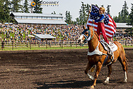 Young girl rides with American flag at Rodeo opening duringt the Under the  Big Sky Music Festival in Whitefish, Montana, USA