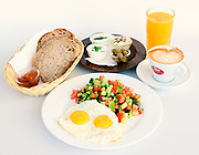 Israeli Breakfast including two fried eggs, salad, bread, butter, cheeses, orange juice and coffee
