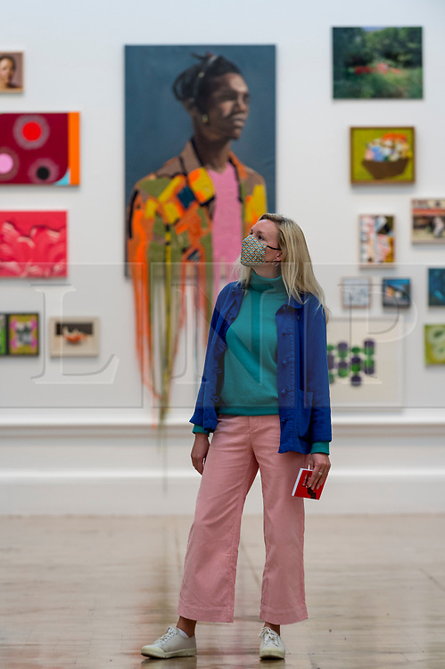 """© Licensed to London News Pictures. 28/09/2020. LONDON, UK. A staff member poses in front of """"Peel"""" by Martin Kerrison.  Preview of the Summer Exhibition at the Royal Academy of Arts in Piccadilly which, due to the Covid-19 lockdown, is taking place for the first time in the autumn.  Over 1000 works in a range of media by Royal Academicians, established and emerging artists, feature in the exhibition which runs from 6 October 2020 – 3 January 2021.  Photo credit: Stephen Chung/LNP"""