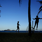 Tight rope walkers silhouetted against the late afternoon sky, practice at Ipanema beach. Rio de Janeiro,  Brazil. 4th July 2010. Photo Tim Clayton....