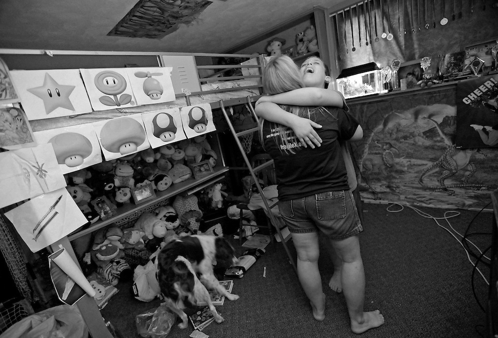 Parker Roos, who suffers from Fragile X, hugs his mother Holly after getting upset about not being able to find one of his inflatable lawn toys at his home in Canton, Illinois, April 3, 2012.   REUTERS/Jim Young