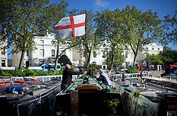 © Licensed to London News Pictures. 04/05/2019. London, UK. Boat owners hoist the English flag, The flag of St George, above their canal boat, during the Canalway Cavalcade festival in Little Venice, West London on Saturday, May 4th 2019. Inland Waterways Association's annual gathering of canal boats brings around 130 decorated boats together in Little Venice's canals on May bank holiday weekend. Photo credit: Ben Cawthra/LNP