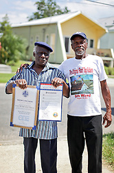29 August 2015. Lower 9th Ward, New Orleans, Louisiana.<br /> Hurricane Katrina 10th anniversary memorials.  <br /> Robert Green, an original Rooftop Rider and survivor of the storm with Ernest Edwards <br /> on Tennessee Street. Green lost his mother and grand daughter to the storm. <br /> Photo credit©; Charlie Varley/varleypix.com.