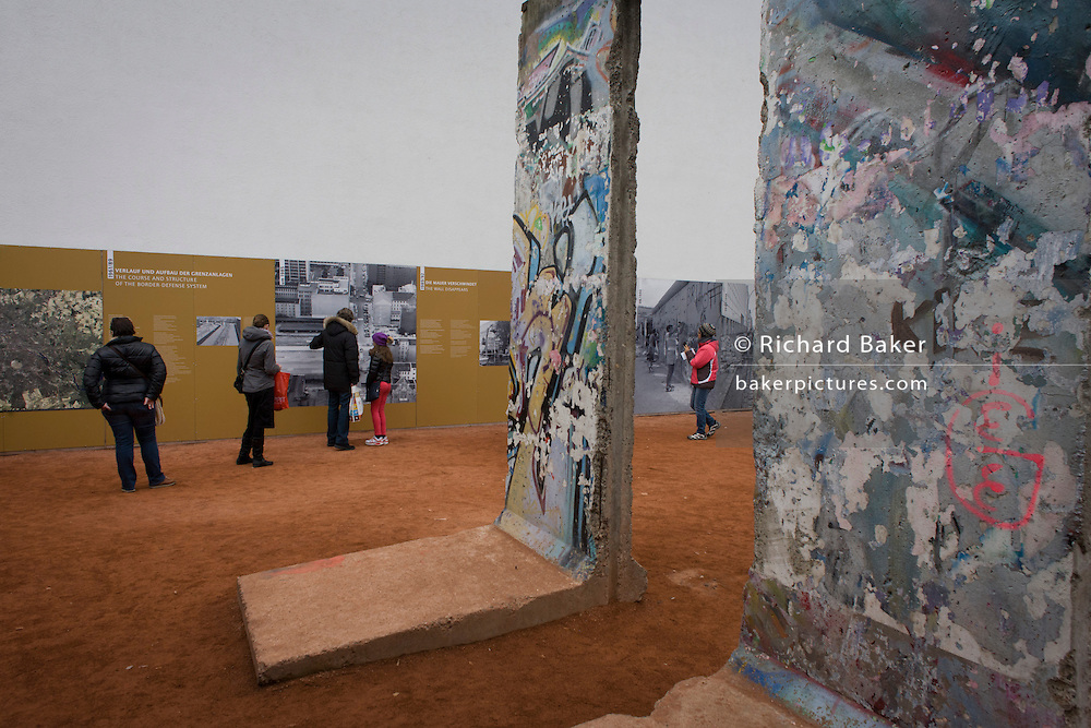 """Under old sections of the Berlin wall, visitors read outdoor exhibition panels near the former Checkpoint Charlie, the former border between Communist East and West Berlin during the Cold War. The Berlin Wall was a barrier constructed by the German Democratic Republic (GDR, East Germany) starting on 13 August 1961, that completely cut off (by land) West Berlin from surrounding East Germany and from East Berlin. The Eastern Bloc claimed that the wall was erected to protect its population from fascist elements conspiring to prevent the """"will of the people"""" in building a socialist state in East Germany. In practice, the Wall served to prevent the massive emigration and defection that marked Germany and the communist Eastern Bloc during the post-World War II period."""