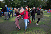 Extinction Rebellion activists wearing red noses dance with each other as the climate camp at Vauxhall is cleared on 15th October 2019 in London, England, United Kingdom. Extinction Rebellion is a climate change group started in 2018 and has gained a huge following of people committed to peaceful protests. These protests are highlighting that the government is not doing enough to avoid catastrophic climate change and to demand the government take radical action to save the planet.