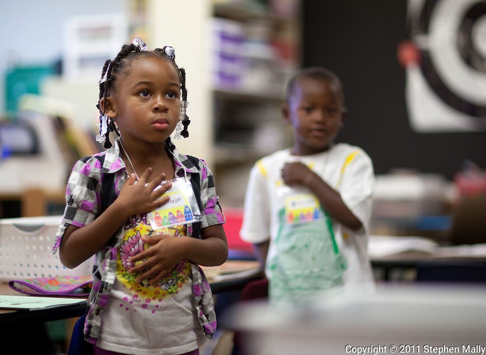 A'Tayjah Phillips, 5, kindergarten, of Cedar Rapids, puts her hand over her heart for the Pledge of Allegiance on the first day of school at Polk Elementary School, 1500 B Avenue NE, in Cedar Rapids on Thursday morning, July 21, 2011.