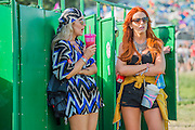 The composting loos are treated much like the loos in a club - chat and make-up.  The 2015 Glastonbury Festival, Worthy Farm, Glastonbury.