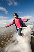 Nine year old Vira Halim-Rotinsulu plays in sea foam whipped up by the wind at the Oregon Coast. (Fully released - 111106)
