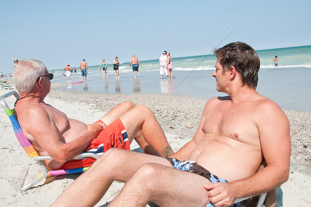 Father and son lounging on the beach watching beachcombers