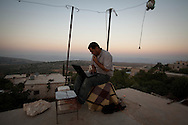 Syrian video activist and journalist Ali uploads the day's video's to his YouTube and Facebook accounts, showing the latest defections of soldiers from the regime army to the Free Syrian Army. Due to the proximinity to Turkey, Ali uses Turkish cellular networks from his rooftop to connect to the internet. al-Basheria, Idlib, Syria.