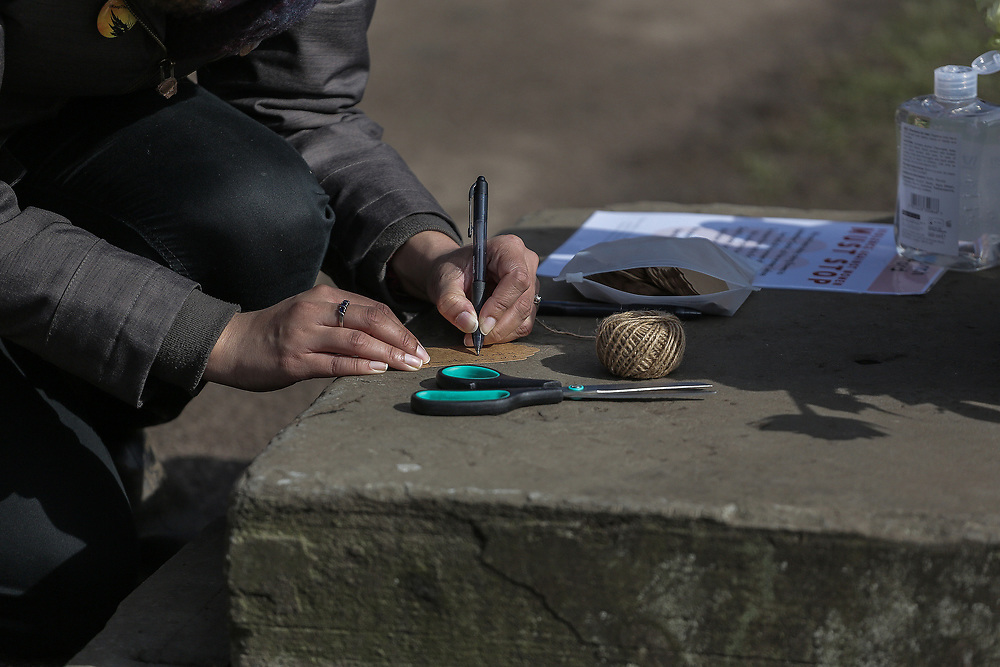 13th, March, 2021. Cheltenham. A member of the public writes a note to attach to a flower in memory of Sarah Everard.