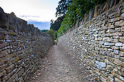 Dry stone walls, drystone, line a country walk path in Swinbrook, The Cotswolds, England, UK