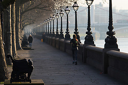 London, February 24th 2016. A runner makes her way along the side of the River Thames on Cheyne Walk as the sun rises on a chilly but clear London morning. ///FOR LICENCING CONTACT: paul@pauldaveycreative.co.uk TEL:+44 (0) 7966 016 296 or +44 (0) 20 8969 6875. ©2015 Paul R Davey. All rights reserved.