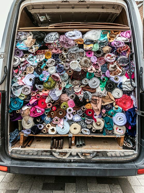 Local trader fills his van with rolls of cloth and textiles after a day selling at his outdoor market stall. The  high street, West Bromwich, West Midlands, UK.