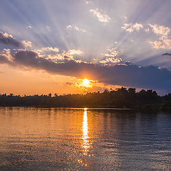Sunset in the area of Hkamti (in the very north of Myanmar). From here, rustic passenger/transport boats are leaving downstream on the Chindwin river. <br /> The Chindwin River is the largest tributary of the Irrawaddy River and originates in the Kachin State of Myanmar and runs south before meeting the Irrawaddy River near the major city (not the capital) Mandalay. Due to low water levels, the Chindwin River is only accessible to larger river vessels during the monsoon season around late July and August and therefore is a much less explored area. Due to the lower number of boats and visitors, the areas around the Chindwin river are peaceful and unspoilt. Most of the river runs through beautiful scenic landscapes, mountain ranges and dense forests.