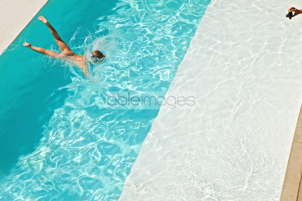 Woman's Hand Taking Photo of Boy Diving into Swimming Pool